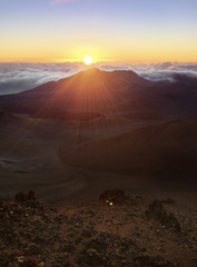 The sun rises above the clouds at the top of an extinct volcano.