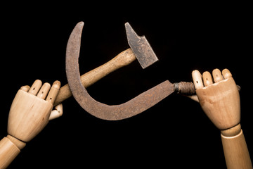 Two wooden hands brandishing a rusty sickle and a used hammer. On black background. With copy-space.