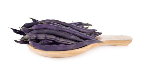 stack of purple beans in wooden big spoon on white background