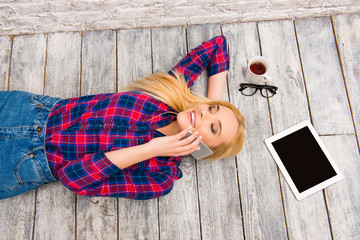 Portrait of young happy girl lying on floor and talking on phone
