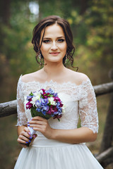 Portrait of bride with bouquet. Young beautiful woman in the forest. Lilac, purple, white, serenity wedding bouquet