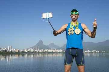 Hashtag gold medal athlete posing for a picture with his mobile phone on a selfie stick at Lagoa Rodrigo de Freitas Lagoon in Rio de Janeiro, Brazil