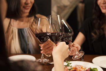 Three young women have been toast with red wine