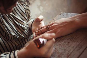 Artist applying henna tattoo on women hands. Mehndi is tradition