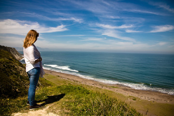 young woman watching waves of picturesque azkorri beach on a ledge of atlantic coast, basque country, spain