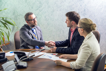 handshake on business meeting at office at the conclusion of the contract