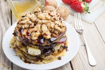 Pancakes with banana , walnut & chocolate on wood background