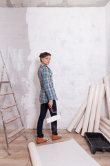 Pretty woman with roller paste wallpaper repair house