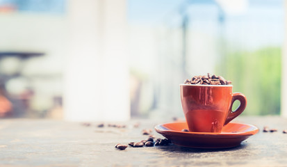 Espresso cup full coffee beans on garden or terrace table over nature background, banner