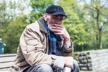 Man smoking cigarette on bench in park.