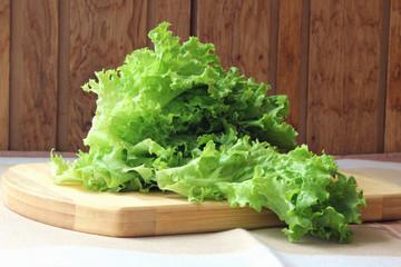 A bunch of lettuce lying on the board..