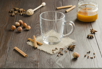 Glass cup of  tea on a linen napkin with cinnamon sticks, honey, nuts and  spice. Blur effect. Background. Copyspace