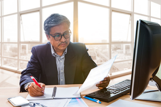 senior working man reading business paper report on working tabl