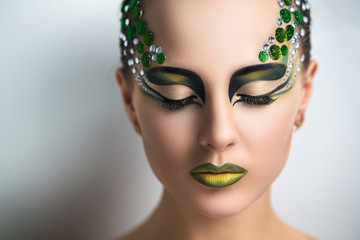 Beautiful young girl, woman, lady, predator, dragon, witch, alien, fairytale. Mythical, stylish look. Bright creative makeup, perfect skin, expressive eyes, color, yellow, green,gems, crystals.