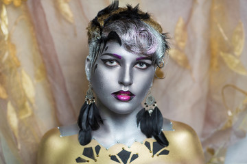 Portrait of beautiful young girl, woman, lady, future, glamour. Ideal creative expressive makeup, silver skin, face, neck, shoulders. Accessory black earrings feathers. Stylish, bright, showy look.