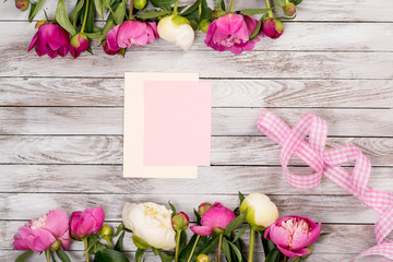 White and pink peonies flowers with pink ribbon and blank card on the white painted wooden planks. Place for text. Square image. Top view.