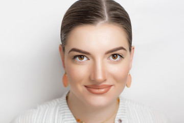 Happy woman with natural make up, slight smile, relaxed face, take care. Photo is good for social advertisement about family love, mother waiting for kids. Peach lipstick same color golden earrings