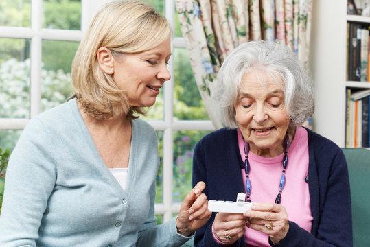 Female Neighbor Helping Senior Woman With Medication