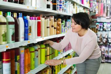 Brunette selecting bottle of shampoo