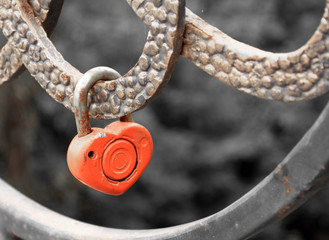 Lock in heart shape on the railing of bridge - a symbol of happy and long married life of bride and groom