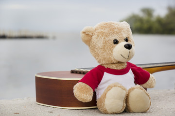 Ukulele and teddy bears on  river side in the evening.