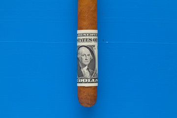 Detail of luxury Cuban cigar with US dollar
