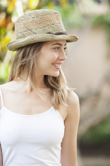 Portrait of a beautiful woman wearing a hat standing in the summer park. Beauty, fashion