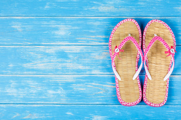 View of flip-flops lying on blue wooden background.