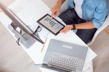 Male with digital tablet studying diagrams
