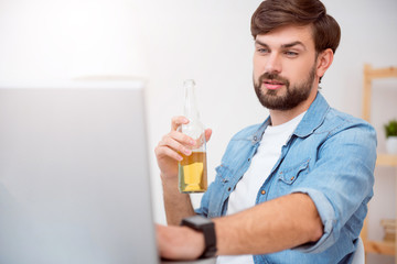 Man working on laptop and drinking beverage