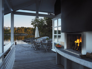 A fireplace in a veranda by the water.