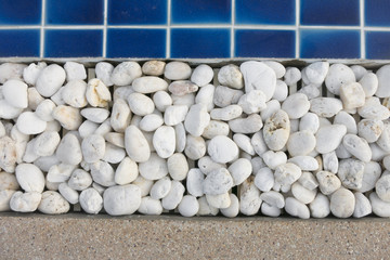small stone decorating on the edge of the swimming pool.