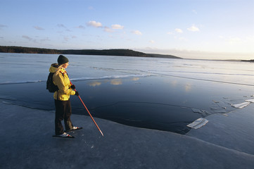Woman wearing long-distance skates standing by a hole in the ice, Sweden.