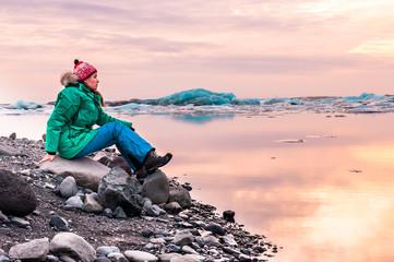 woman sitting on the beach of glacial lagoon, Iceland. Jokulsarlon Glacier Lagoon