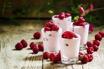 Homemade Pink Raspberry yogurt with fresh berries in glasses, vi