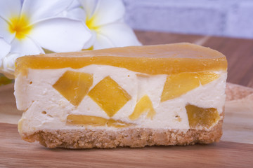 Mango Cheese Cake n plate wooden and Plumeria flower with rustic