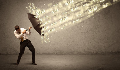 Business man holding umbrella against dollar rain concept