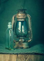 Rusty kerosene lamp and a bottle of kerosene