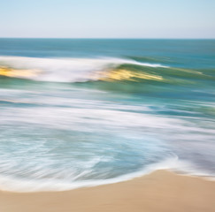 Fototapete - Golden Wave Blur.  An ocean wave with blurred panning motion and golden sun reflections.