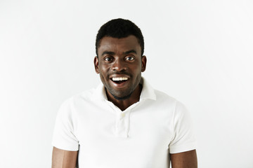 Amazed African American student in casual shirt looking at the camera with happy and surprised expression, after passing final exams at university with excellent marks. People and lifestyle concept