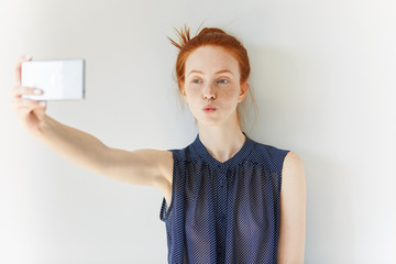 Portrait of beautiful redhead girl wearing spotted dress making self-portrait using cell phone, sending a kiss. Young female with freckles taking pictures against white wall. Selective focus