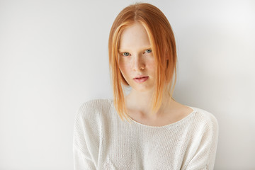Beautiful female teenage model wearing casual white top looking at the camera with thoughtful expression on her face. Isolated portrait of shy redhead student girl with freckles and no make up