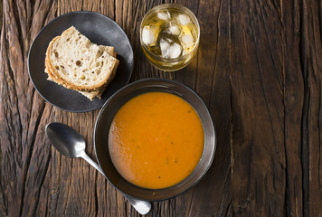 Tomato soup on a rustic wooden table.