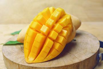 ripe mango with mango leaf in wooden background.
