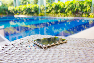 Smartphone put on armchair beside the pool