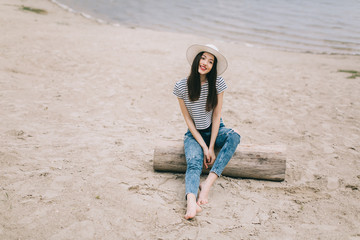Beautiful stylish and fashionable girl in a hat posing on a beach.