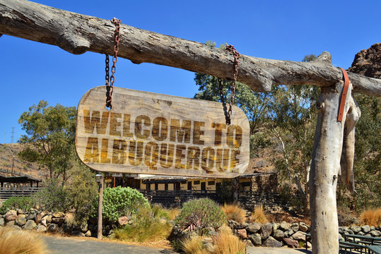 """old wood signboard with text """" welcome to albuquerque"""" hanging on a branch"""