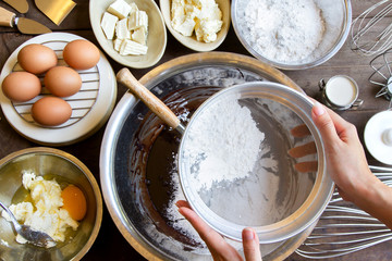 Hand Sift flour, prepare for cooking Chocolate brownie cake at bakery, Top view
