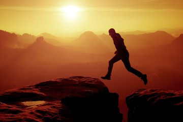 Young crazy man jump on mountain peak. Silhouette of jumping man