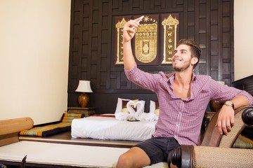 A handsome young man taking a selfie in a asian style hotel room..